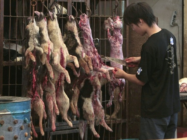 A vendor skins dogs at a food market in Nanjing